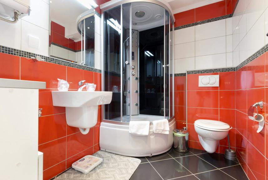 Czerwono-biała łazienka z prysznicem z hydromasażem