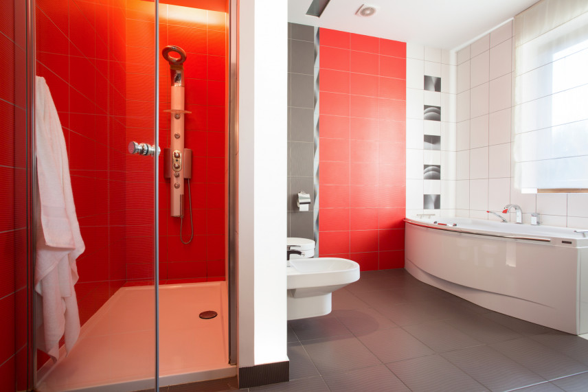 Czerwona łazienka z prysznicem i wanną.