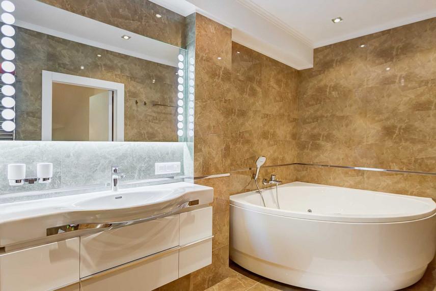 Łazienka z narożną wanną i dużym lustrem