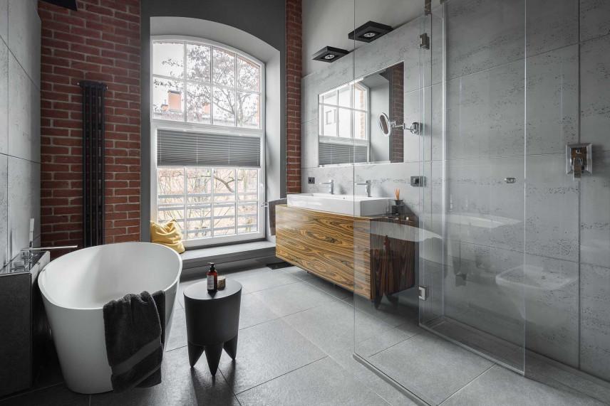 Szara łazienka ze ścianą z cegły
