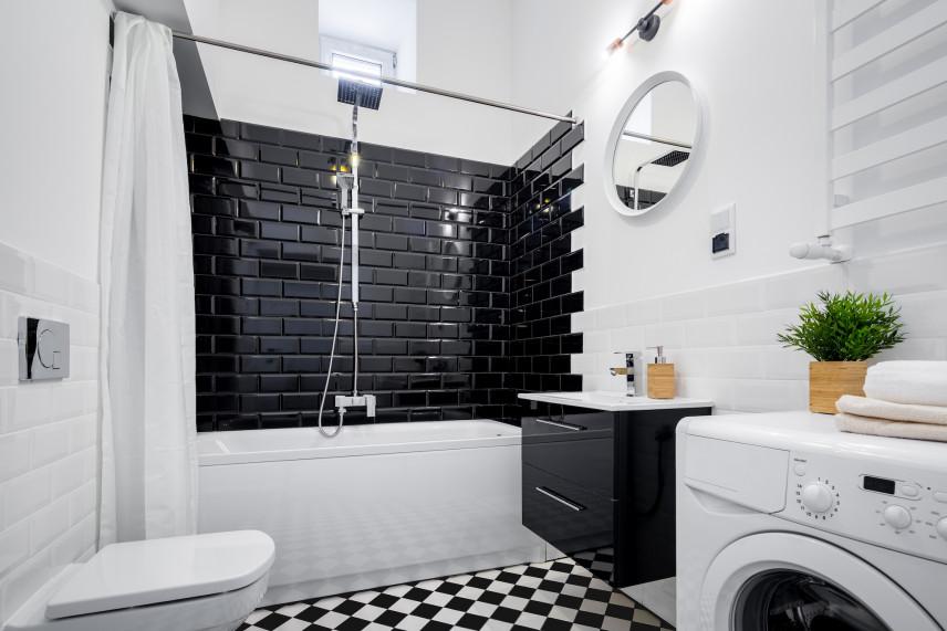 Czarno-biała łazienka ze  ścianą z czarnych cegieł