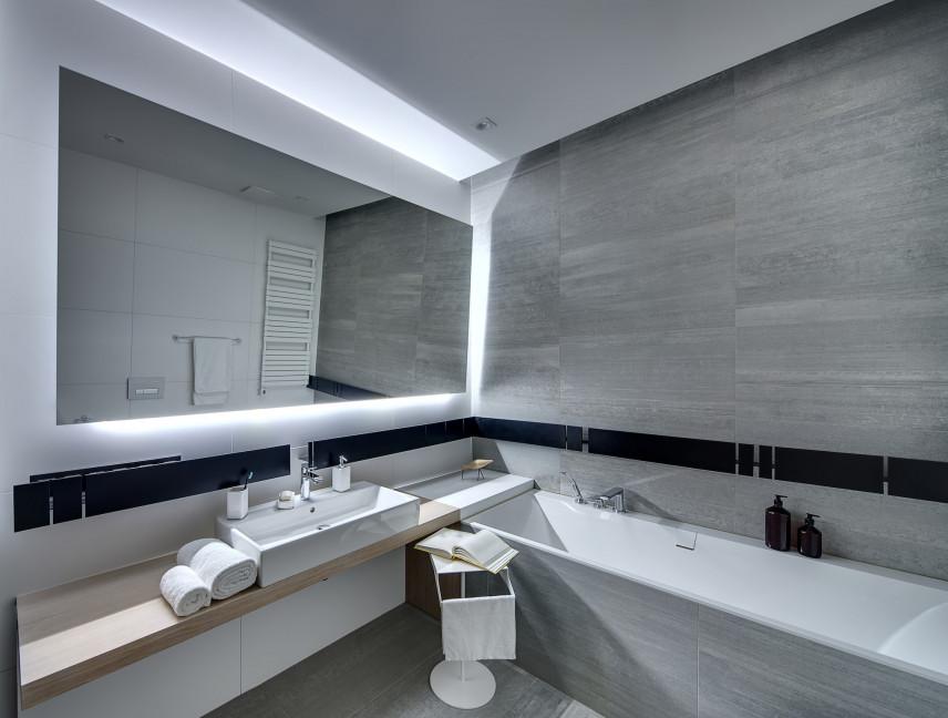Łazienka z szarą ścianą  i dużym lustrem