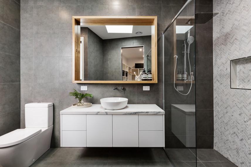 Szara łazienka z designerskim lustrem