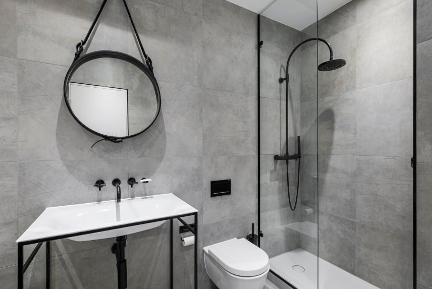 Łazienka w kolorze szarym z okrągłym lustrem