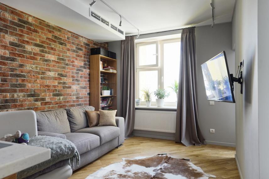 Szary salon z cegłą na ścianie