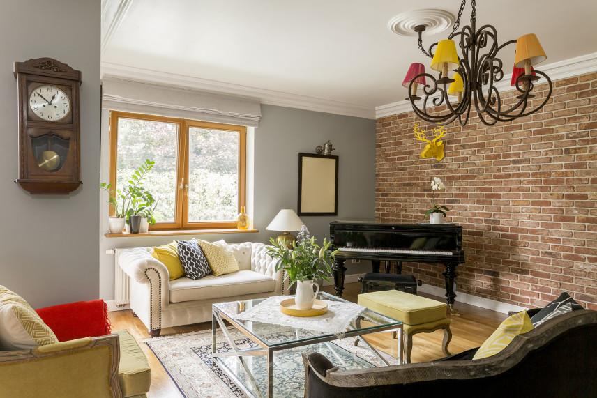Salon z cegłą na ścianie i kolorowym żyrandolem