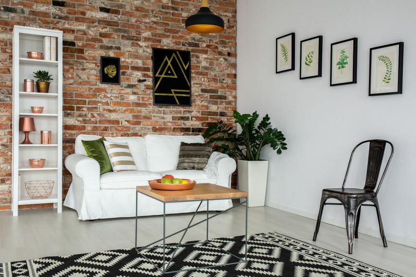 Salon z cegłą na ścianie i dywanem