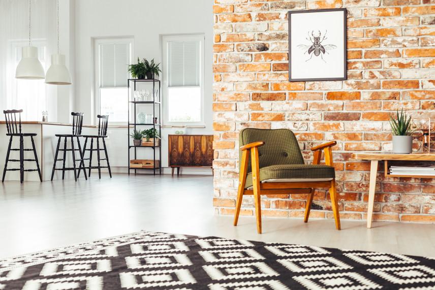 Salon w stylu skandynawskim ze starą cegłą na ścianie