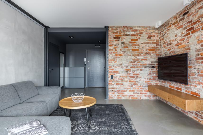 Nowoczesny salon  z betonowa podłogą i cegłą na ścianie