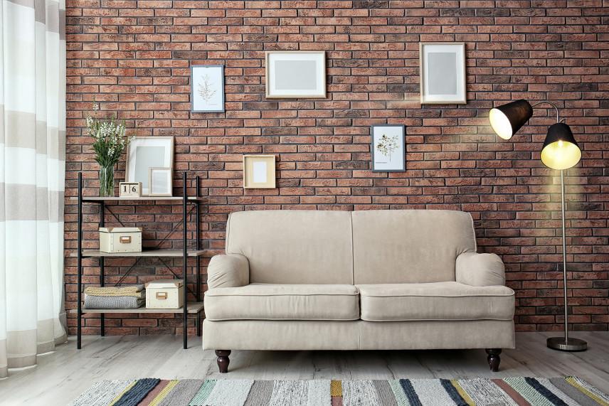 Salon z beżową kanapą i ceglana ścianą w tle