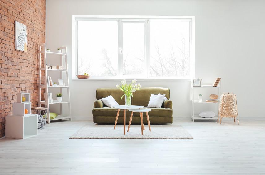 Jasny, designerski salon z cegłą na ścianie