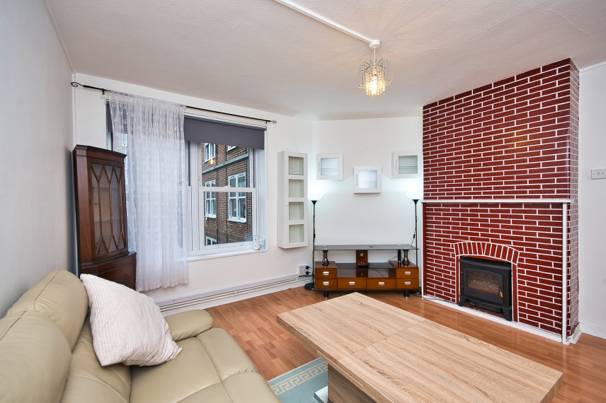 Mały salon z kominkiem na ceglanej ścianie