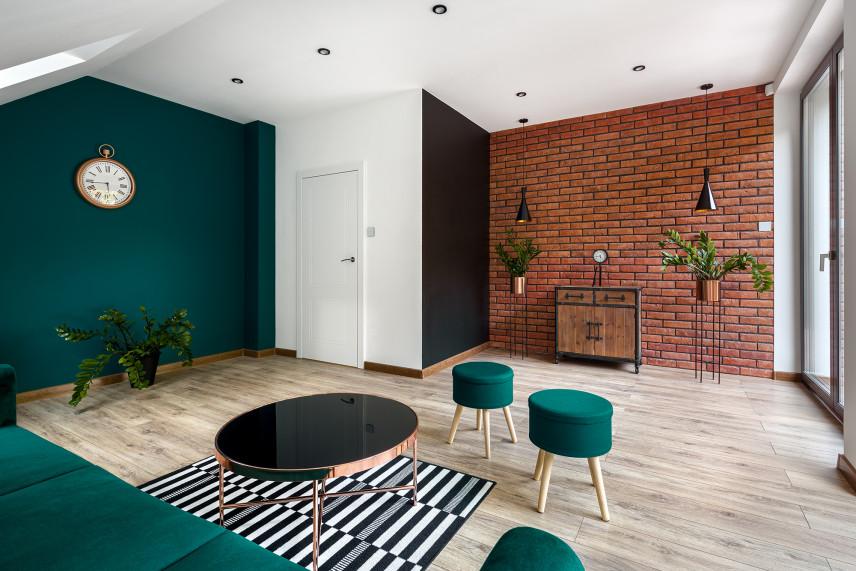 Salon z zielonymi meblami i ścianą z cegły