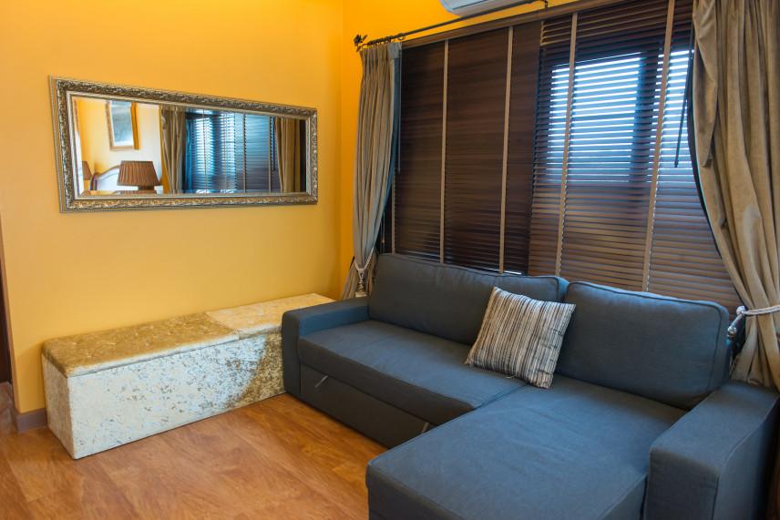 Salon z granatową kanapą i żółtą ścianą