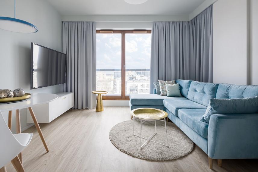 Salon z telewizorem i błękitna kanapą