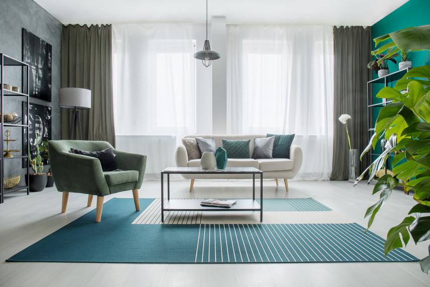 Salon z zieloną ścianą i turkusowym dywanem