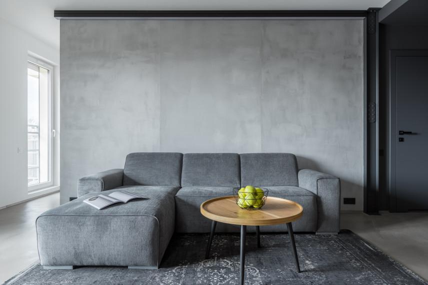 Szary salon z betonową ścianą