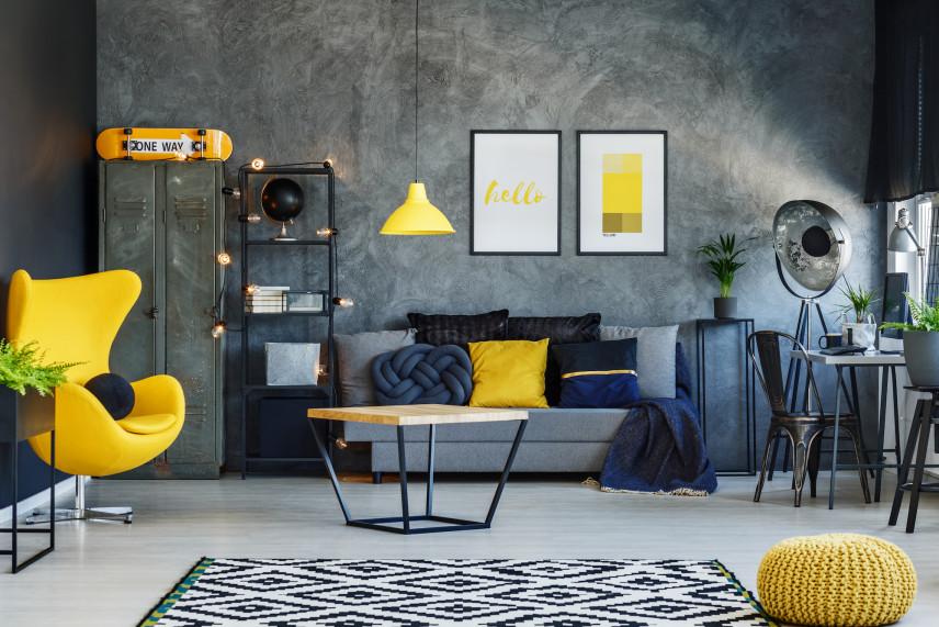 Salon z szarą ścianą  i żółtymi dodatkami