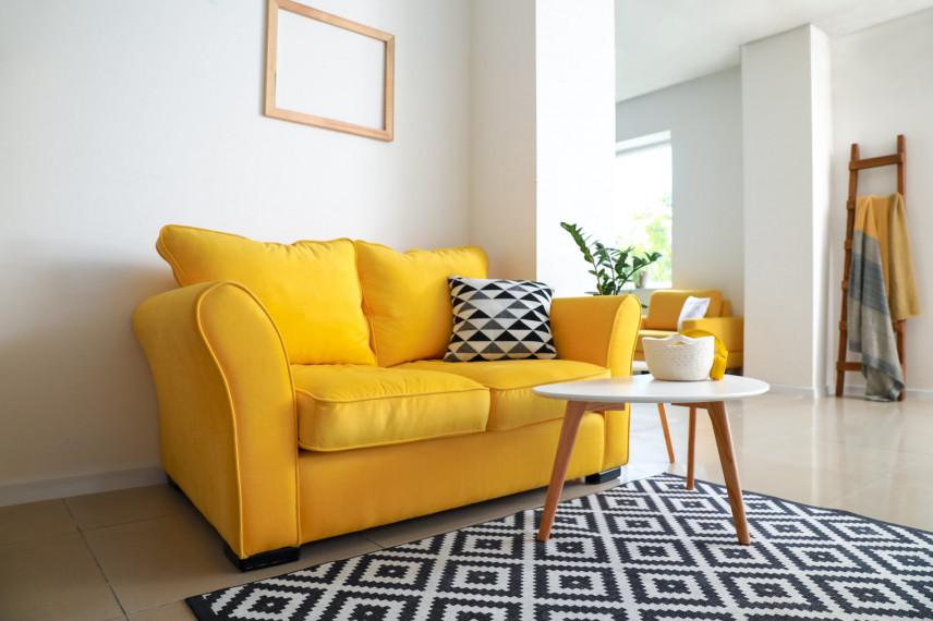 Żółta sofa z biało-czarnym dywanem