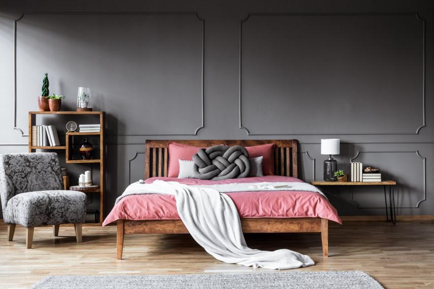 Sypialnia z drewnianym łóżkiem na nóżkach