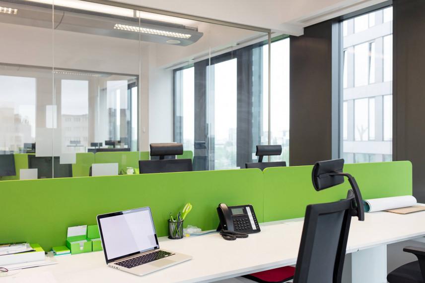 Open space z zielonym biurkiem