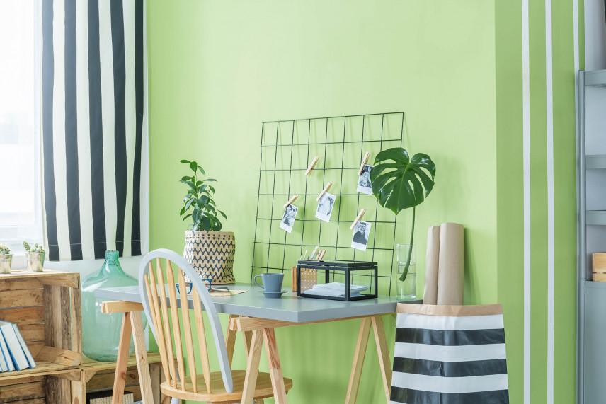 Małe biurko przy zielonej ścianie