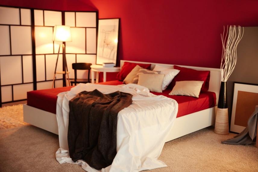 Białe łóżko w czerwonej sypialni