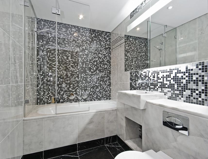 Łazienka z marmurową wanną i czarno-białą mozaiką