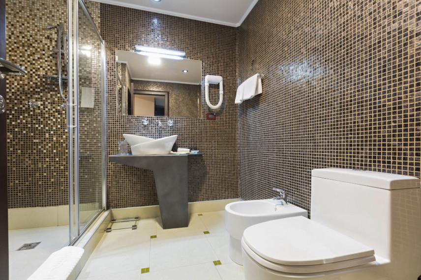 Łazienka z brązową mozaiką na ścianie