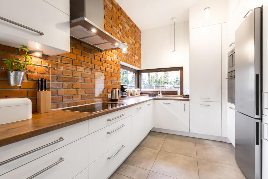 Kuchnia w kształcie L z cegłą na ścianie