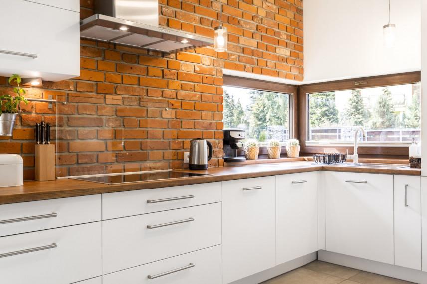 Biała kuchnia z cegłą na ścianie