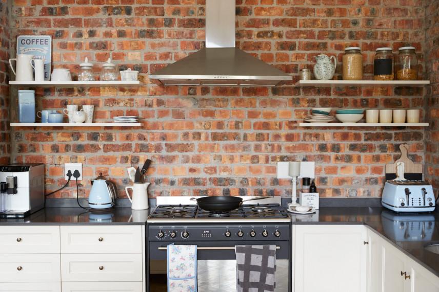 Kuchnia z ceglaną ścianą i okapem