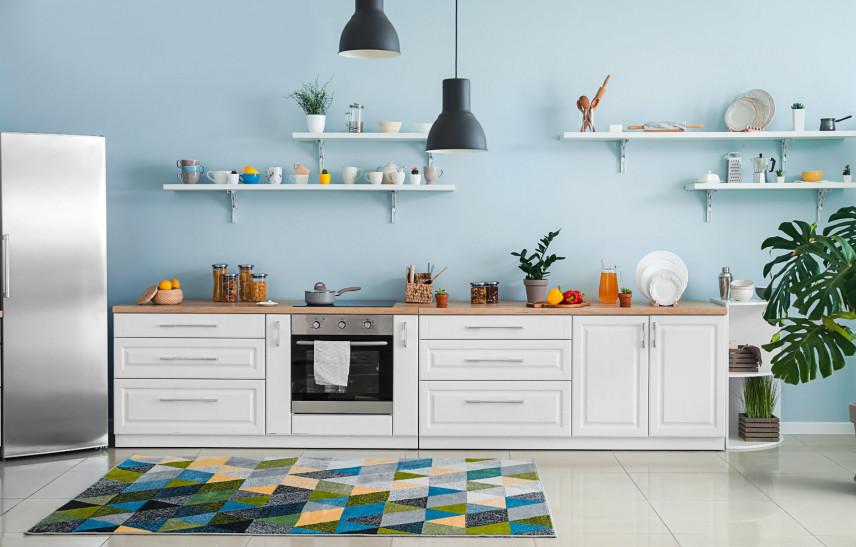 Kuchnia z błękitną ścianą i białymi meblami