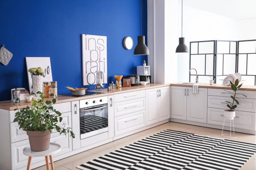 Nowoczesna biała kuchnia z niebieska ścianą