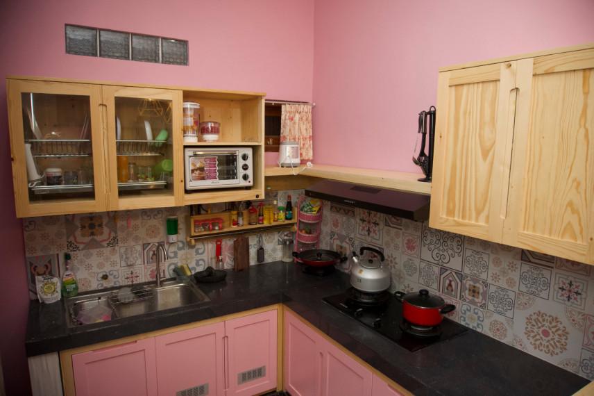 Różowa kuchnia z czarnymi blatami