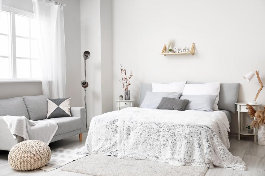 Łóżko małżeńskie i sofa w sypialni
