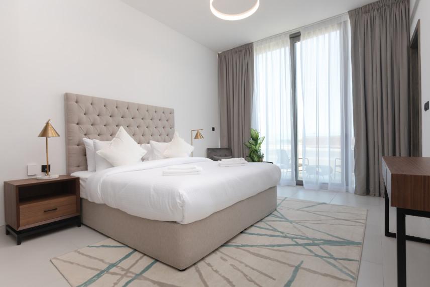 Beżowe łóżko z tapicerowanym i pikowanym zagłówkiem