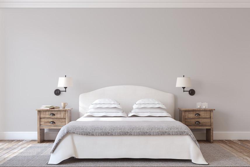 Białe łóżko na tle beżowej ściany