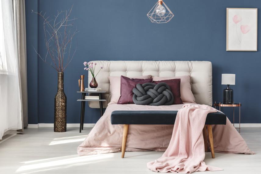 Białe łóżko na tle niebieskiej ściany