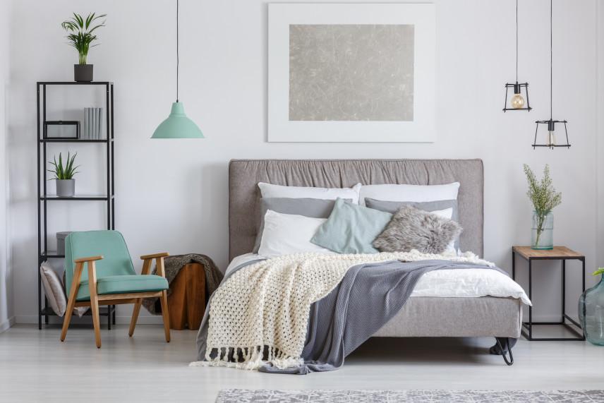 Szare łóżko na tle białej ściany