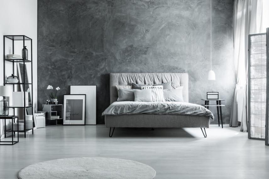 Szare łóżko na tle betonowej ściany