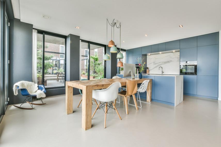 Niebieska kuchnia z drewnianym stołem