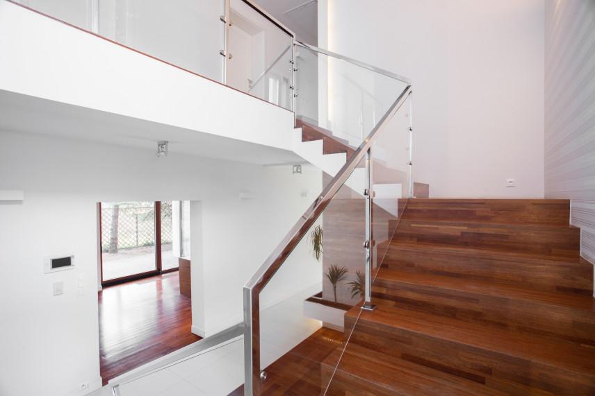Przestronny, biały przedpokój ze schodami