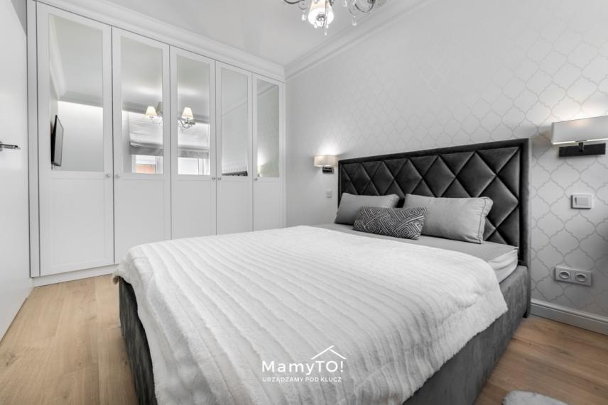 Biała szafa z lustrem w sypialni