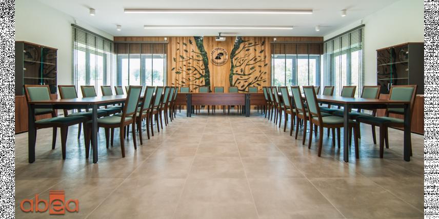 Aranżacja sali konferencyjnej z drewnianym elementem na ścianie