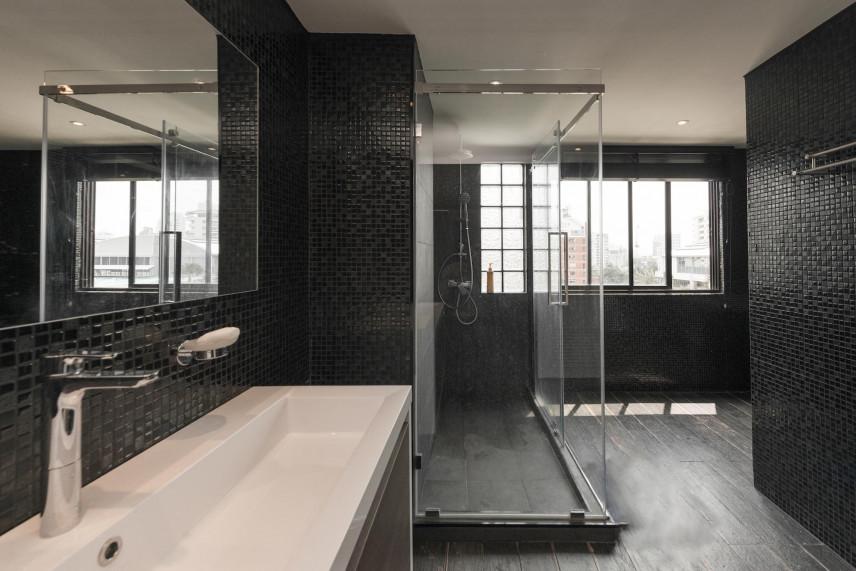 Łazienka z czarnymi płytkami i dużym oknem