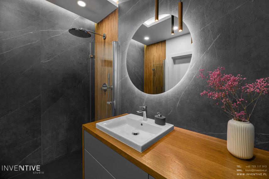 Łazienka z okrągłym lustrem i drewnem na ścianie