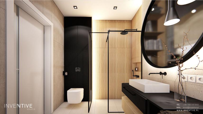 Łazienka z czarnym blatem i drewnianą ścianą