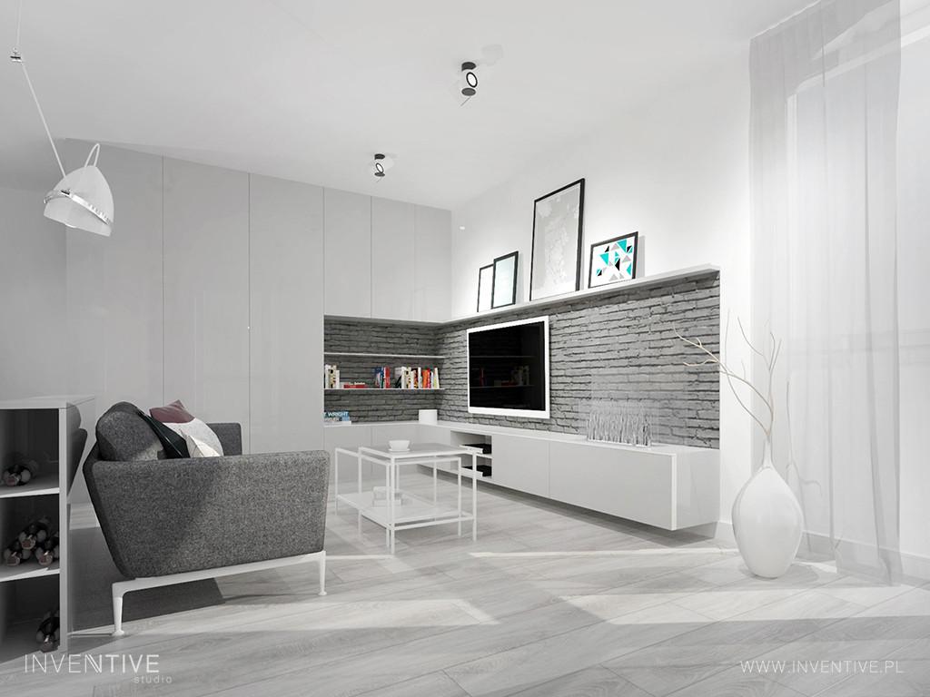 Biały salon z szarą cegłą na ścianie