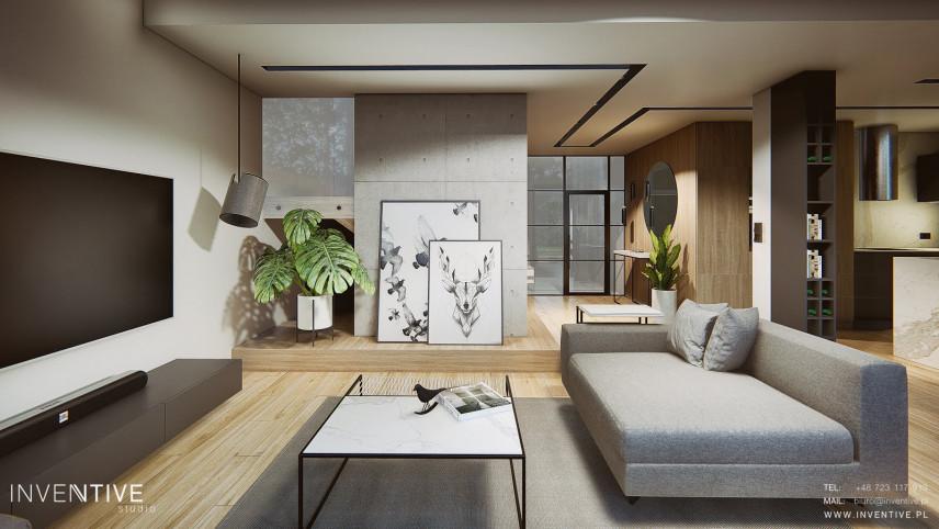 Salon  z telewizorem i ścianą z dekoracyjnego betonu
